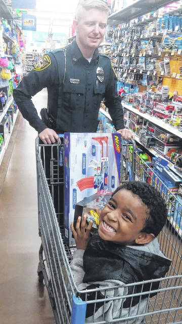 Fairmont Police Officer Ryan Gibson Helps Kiante Moody 7 Do Some Shopping At Walmart On Friday As Part Of The Departments Shop With A Cop Program