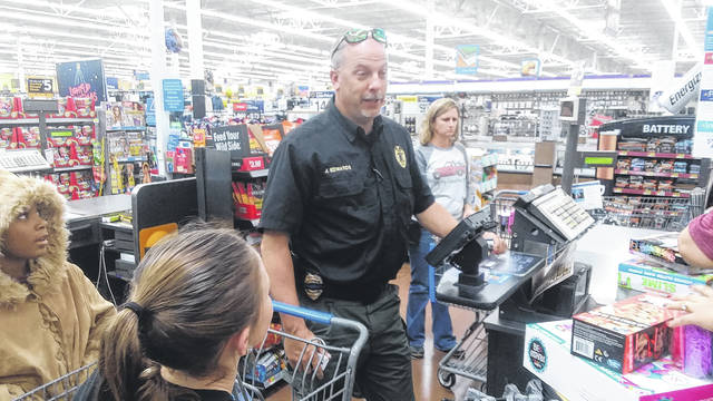 Fairmont Police Chief Jon Edwards Prepares Friday To Pay The Bill At Wal Mart In Pembroke End Of Shop With A Cop Program