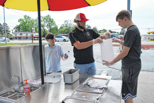 Tucker Scott, left, Aaron West, middle, and Jackson Scott stand ready Tuesday to complete orders at The Hot Dogg Cart outside the Village Station Restaurant on Roberts Avenue in Lumberton. The cart, operated by the restaurant, is open from 10:30 a.m. to 2 p.m. Mondays, Tuesdays, Thursdays, Fridays and Saturdays. First responders, postal workers and truckers can their choice of two hot dogs or two corn dogs and a drink for free at the stand.