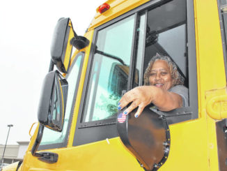 Lumberton Senior High School bus driver Shirley Hill places a mobile hot spot device on a bus parked at the Food Lion on West Fifth Street in Lumberton on Wednesday. The bus is one of 10 used in the Park and Learn Program that provides free Wi-Fi to community members and students who park near the buses in parking lots across the county.