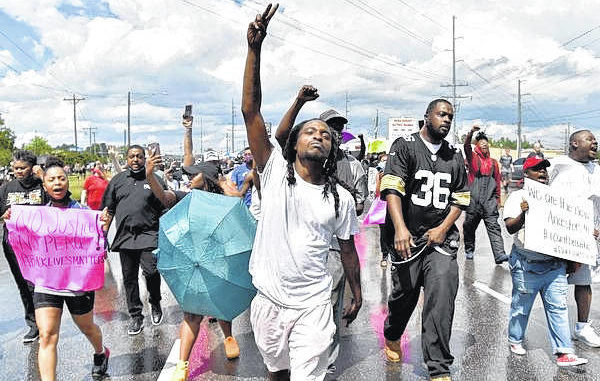 Organizer Rakeem Jones leads a peaceful march Saturday down Skibo Road in Fayetteville to protest the death of George Floyd in Minnesota. Mayor Mitch Colvin is at left.                                  Courtesy photo | Ed Clement/The Fayetteville Observer