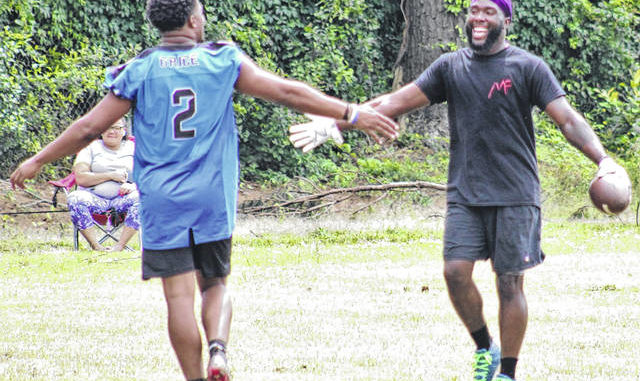 Jonathan Bym | The Robesonian                                 Robeson County Bears quarterback Braylan Grice, left, celebrates a touchdown pass to Bryan Carpenter during a 7-on-7 scrimmage on Sunday. The Bears semi-pro football team features several local products, including this pair of former Lumberton standouts.