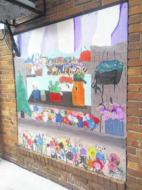<p>Tomeka Sinclair   The Robesonian</p>                                 <p>Shown is one of the painted wooden panels that now covers an old, boarded window in an alleyway in downtown Lumberton. The painting, completed by St. Pauls High School art students and teachers, depicts a storefront with flowers and candy.</p>