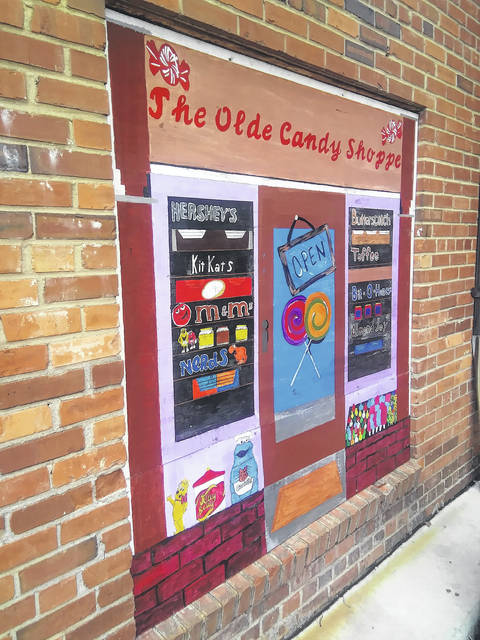<p>Tomeka Sinclair   The Robesonian</p>                                 <p>Shown is one of the painted wooden panels that now cover an old, boarded window in an alleyway in downtown Lumberton. The painting, completed by St. Pauls High School art students and teachers, depicts an old candy shop storefront.</p>