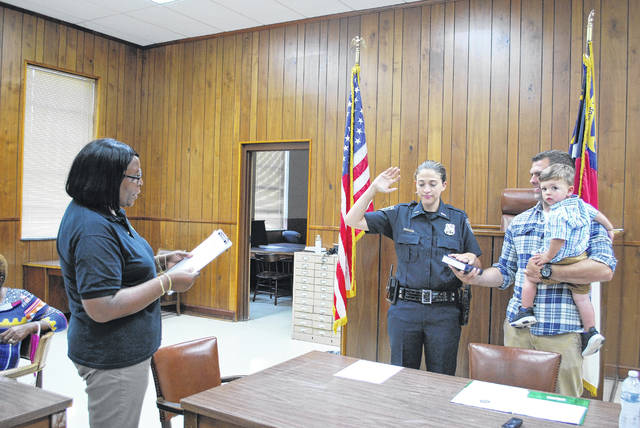<p>St. Pauls Magistrate Shirley McMillan, left, reads the oath of office Thursday evening during a swearing-in ceremony for police Officer Jennifer Mathna, while her husband, Zachary Mathna, holds the Bible and their 1-year-old son Collin. The ceremony took place during a regular town Board of Commissioners meeting.</p>