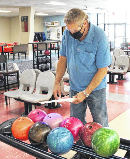 <p>Jonathan Bym | The Robesonian</p>                                 <p>David McLamb, a worker at the Lumberton Bowling Center, uses a UV wand to sanitize rental bowling balls after customers finished their round on Friday. With the bowling center reopening, cleaning the center has taken on a bigger job for the employees.</p>