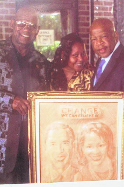 <p>Shown is Terrence Hill and his wife, Nicole, standing with the late U.S. Congressman John Lewis about 15 years ago. Hill, a Red Springs-based leather artist holds one of his works featuring former president and first lady Barack and Michelle Obama.</p>
