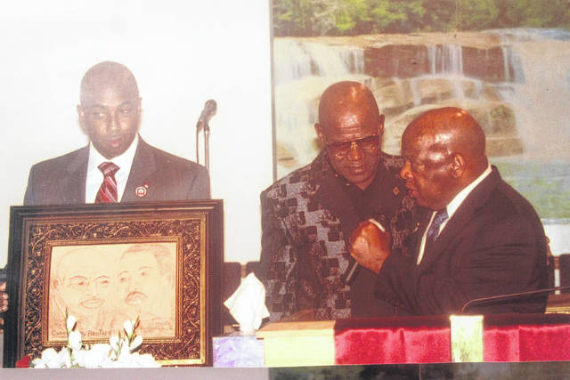 """<p>Shown is leather artist Terrence Hill presenting a work titled """"Carry on My Brother"""" to the late U.S. Congressman John Lewis. The image features Lewis with Rev. Martin Luther King Jr.</p>"""