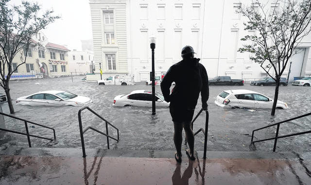 Floodwaters move Wednesday on a street in downtown Pensacola, Florida. Hurricane Sally made landfall Wednesday near Gulf Shores, Alabama, as a Category 2 storm, pushing a surge of ocean water onto the coast and dumping torrential rain that forecasters said would cause dangerous flooding from the Florida Panhandle to Mississippi and well inland in the days ahead.                                  AP photo | Gerald Herbert