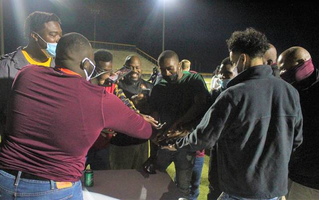 <p>Chris Stiles | The Robesonian</p>                                 <p>Lumberton players and coaches huddle up for a photo-op while wearing their state championship rings after the team's ring ceremony Monday at Alton G. Brooks Stadium.</p>