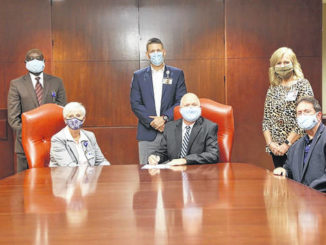Southeastern Health board of trustees Chair Kenneth Rust signs a nonbinding letter of intent with UNC Health to enter into a long-term comprehensive Management Services Agreement. Present at the signing were, seated at left, SeHealth President/CEO Joann Anderson and, seated at right, SeHealth board Vice Chair Wayland Lennon. Standing, from left, are SeHealth Vice President and Chief Engagement Officer Patrick Ebri, Vice President and Chief Operating Officer Jason Cox, and Chief Nurse Executive Renae Taylor.                                  Courtesy photo   Southeastern Health