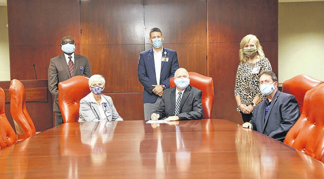 Southeastern Health board of trustees Chair Kenneth Rust signs a nonbinding letter of intent with UNC Health to enter into a long-term comprehensive Management Services Agreement. Present at the signing were, seated at left, SeHealth President/CEO Joann Anderson and, seated at right, SeHealth board Vice Chair Wayland Lennon. Standing, from left, are SeHealth Vice President and Chief Engagement Officer Patrick Ebri, Vice President and Chief Operating Officer Jason Cox, and Chief Nurse Executive Renae Taylor.                                  Courtesy photo | Southeastern Health