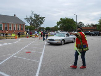 Curbside Official Shirelle Walters directs traffic Thursday afternoon at the early voting site in the Pine Street Senior Citizens Building, located 801 N. Pine St. in Lumberton. Handicap parking and curbside voting are available only in the building's parking lot.
