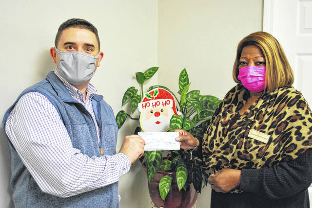 <p>Dyana McKenzie, an advertising representative for The Robesonian, right, receives Thursday a $500 donation to the Empty Stocking Fund from Trinity Holiness Church Pastor Jami Lewter.</p>