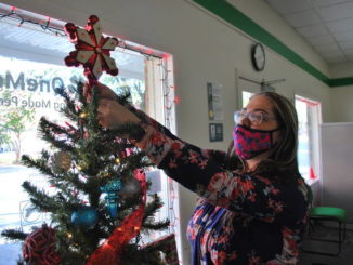 OneMain Financial Loan specialist Erica Hollenbeck straightens the tree topper on the company's Christmas tree Monday. The tree is displayed by the window at the loan service office on Elm Street in Lumberton and is an annual tradition that is decorated each year after the Thanksgiving holiday.