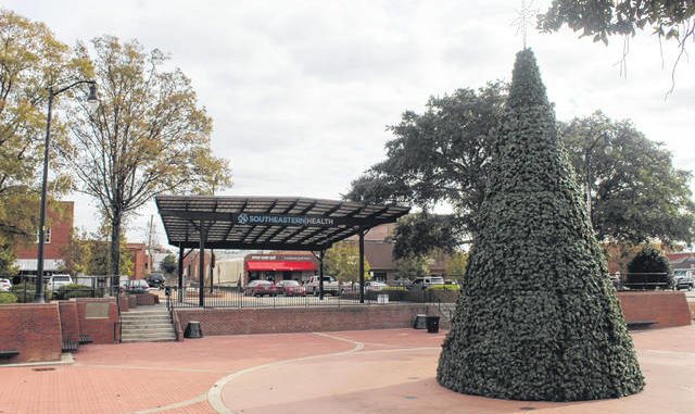 The 35-foot Christmas tree is lit and on display at Lumberton's downtown plaza despite the cancellation of the annual tree lighting ceremony. The tree lighting and other downtown holiday traditions have been canceled because of the COVID-19 pandemic.                                  Tomeka Sinclair | The Robesonian