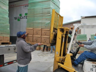 Lorenzo Wilson, left, and Larry Thompson, unload some of the 1,400 boxed meals from Mountaire Farms that were delivered Monday to the Lumberton Housing Authority to be distributed to needy families across the county.