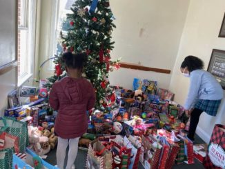 Two children shop for toys at the Maxton Police Department on Tuesday during the department's Shop With A Cop event, which distributed Christmas gifts to about 50 children in the community.
