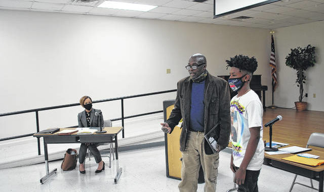 Fairmont Mayor Charles Townsend, left, presents the Hero Award to Devon Williams during Tuesday's Board of Commissioners meeting in the Fairmont-South Robeson Heritage Center. The town honored Williams for the courage he exhibited while defending his sister during a shooting incident in October.                                  Jessica Horne | The Robesonian