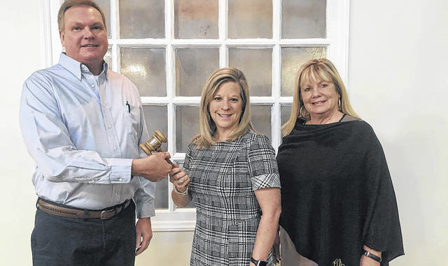 Past chair of the Lumberton Chamber of Commerce board of directors Bryan Britt, left, passes the gavel to 2021 board Chair Maureen Metzger as Chamber Executive Director Cindy Kern watches.                                  Courtesy photo