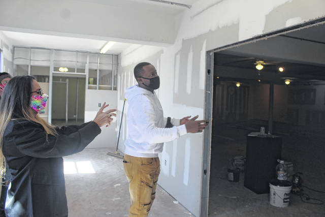 <p>Tomeka Sinclair   The Robesonian</p>                                 <p>Melvin Morris, the owner and curator of the Inner Peace Center for the Arts, and Sara Voecks, the center Marketing and Arts director, show where double doors will be installed at the old Kimbrell's Furniture store, which is being renovated to hold the arts center.</p>