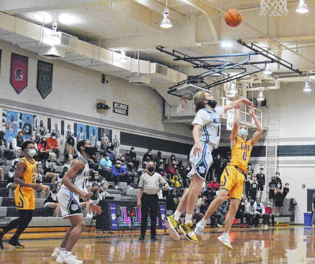 <p>Contributed photo</p>                                 <p>Lumberton's Charlie Miller, 0, attempts a 3-point shot over Millbrook's Redford Dunton, 14, during Tuesday's NCHSAA 4A East Regional final in Raleigh.</p>