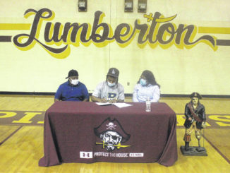 Chris Stiles | The Robesonian                                 Lumberton's Davieyon King-McAllister signs to play collegiately at Bluefield State College during a ceremony Wednesday in Lumberton. He is joined by his parents.