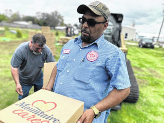 Red Springs Electric Utilities employee Joseph Locklear helps Wednesday to unload boxes of chicken donated by Mountaire Farms at John M. McNeill Farmers Market. Locklear was among the many people who helped load boxes of donated Easter meals into vehicles to be taken to churches and organizations for distribution to families in need.