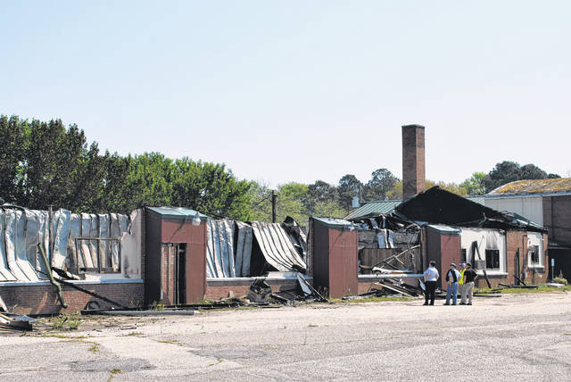 <p>Stephanie Chavis, Robeson County fire marshal and Emergency Management director, left, stands Wednesday morning with Earney Hammonds, director of the Public Schools of Robeson County's Maintenance Department and first responders as they discuss damages to a building that once contained classrooms at the vacant R.B. Dean Elementary School campus in Maxton.</p>