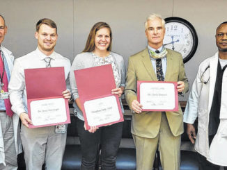 Dr. Samuel Fleishman, left, and Dr. Chuck Chima, right, present Resident of the Quarter Dr. Ryan Huttinger, second from left, Advanced Practice Provider of the Quarter Nurse Practitioner Meaghan Eddy, and Physician of the Quarter Dr. David Stewart with their certificates at the May 3 Cape Fear Valley Medical Staff meeting.                                  Courtesy photo   Cape Fear Valley Health