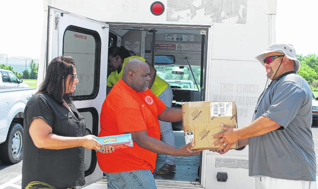 Robeson County Parks and Recreation Department Director Wendy Chavis, left, looks on Monday as program specialists Anthony Govan, middle, and Sean Locklear load recreation materials onto the department's mobile unit. The department will host its first Mobile Recreation Program on Friday in Maxton.                                  Jessica Horne   The Robesonian