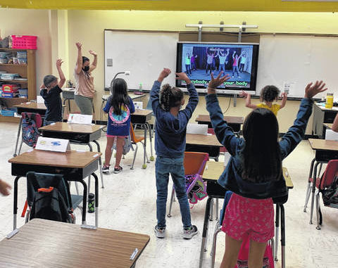 """Kim Demery, a kindergarten teacher at Pembroke Elementary School, second from left, leads a """"brain break"""" session Tuesday for students in attendance of the Public Schools of Robeson County's Summer Learning and Enrichment Camp."""