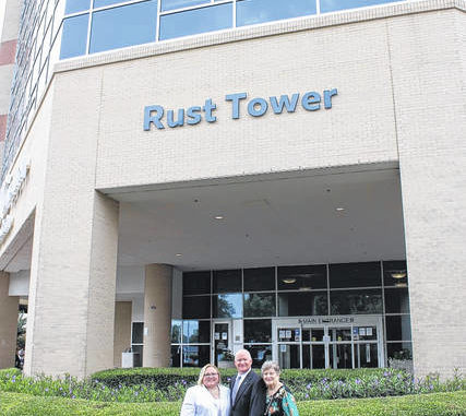 Lisa, left, Kenneth and Mary Anne Rust stand Monday under the new signage featuring their family name on the seven-story patient bed tower in Lumberton. The UNC Health Southeastern's board of trustees dedicated the health system's tower as the Rust Tower during a ceremony Monday in recognition of the contributions of the Rust family over the past 35 years.                                  Courtesy photo | UNC Health Southeastern