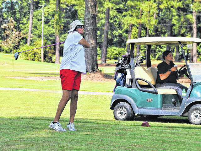 <p>Chris Stiles   The Robesonian</p>                                 <p>Pandora Carter hits her tee shot on the 17th hole during Saturday's round at the Robeson County Golf Championship as playing partner Amy Maynor looks on. Carter leads the Ladies Division.</p>
