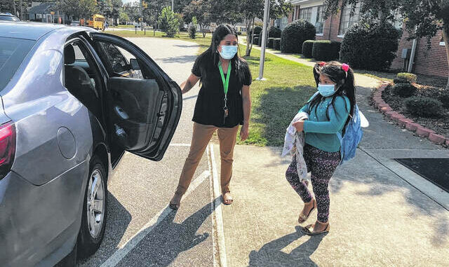Nayeli Estrada, a Rowland Norment Elementary instructional assistant and intern for kindergarten classes, left, helps first-grader Aylen Baltazar to her vehicle at dismissal on Tuesday. The school has about 400 students and requires all students wear masks in accordance with the Public Schools of Robeson County's Board of Education policy approved Tuesday.                                  Jessica Horne   The Robesonian