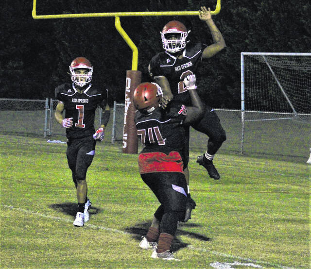 <p>Chris Stiles   The Robesonian</p>                                 <p>Red Springs' Angel Washington (2) and Jauan Stubbs (74) celebrate after Washington's touchdown run during Friday's game against Midway in Red Springs.</p>